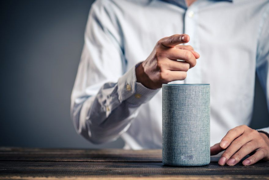 A man shows with his forefinger to you and in front of him is a smart speaker